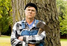 Man-holding-an-axe-leaning-against-a-tree.jpg